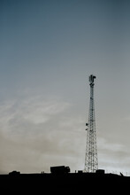 Low Angle Silhouettes Of Tall Telecommunication Tower And Vehicles On Hill Against Gray Cloudy Sky In Evening In Morocco