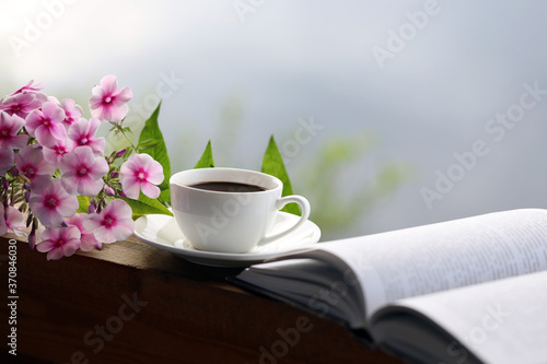 Foto cup of coffee, book and flowers on the table