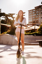 Smiling Female In Stylish Wear Riding Modern Electric Scooter And Enjoying Sunny Weather In City