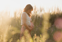 Side View Of Pregnant Female Touching Belly While Standing In Tall Grass During Sunset In Meadow