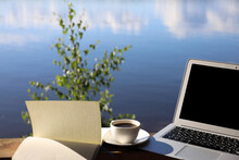 Coffee Cup, Laptop And Writing On The Background Of The Sky And The River, Remote Work In The Country
