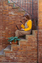 Young Woman With Laptop Using Smart Phone While Sitting On Steps