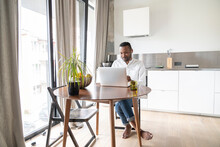 Portrait Of Man Sitting At Table In Modern Apartment Using Laptop And Earphones