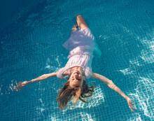 Germany, Brandenburg, Teenage Girl Floating In Pool