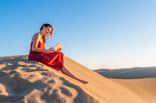 Woman In Red Dress Sitting In The Dunes Using Tablet, Gran Canaria, Spain