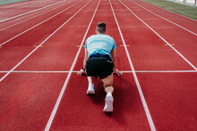 Male Athlete In Starting Position On Tartan Track