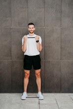 Male Athlete Practicing With Resistance Band In Front Of A Wall
