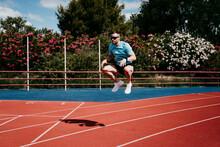Male Athlete Jumping On Tartan Track