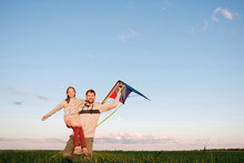 Man Holding Kite Carrying Happy Daughter While Standing On Green Landscape