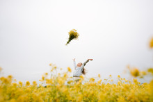 Smiling Girl Throwing Bouquet Of Rape Flowers Up