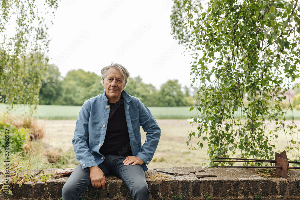 Senior man sitting on a brick wall in the countryside