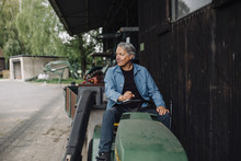 Senior Man Driving Tractor With Trailer On A Farm