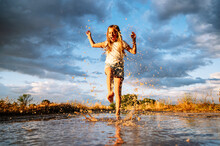Cheerful Girl Splashing Water On Puddle Against Cloudy Monsoon Sky