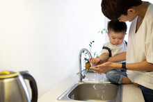 Mother Washing Cute Son's Hands In Kitchen Sink At Home