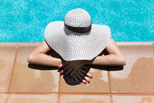 Young Woman Wearing Hat Relaxing At Poolside During Sunny Day