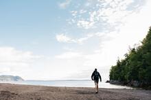 Man Walking Towards Sea At Beach