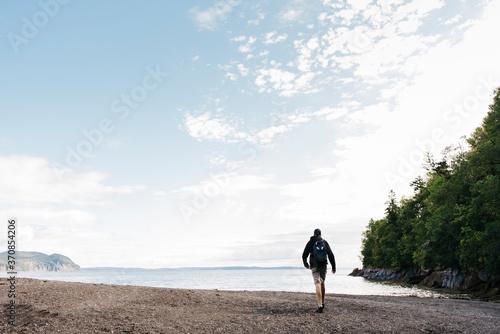 Man walking towards sea at beach - 370854206