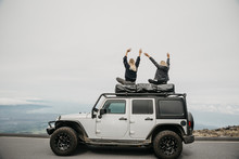 Female Friends Enjoying View While Sitting On Top Of SUV At Maui, Hawaii, USA