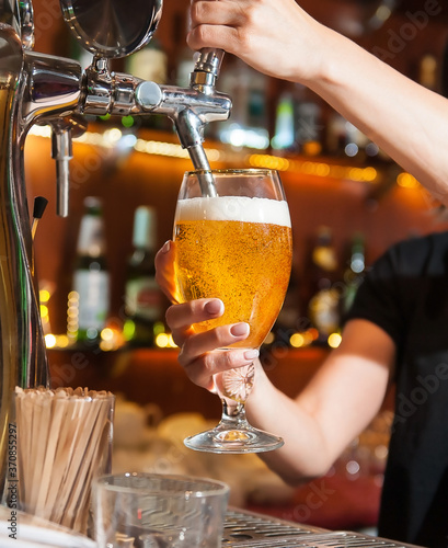 Photo Beer pouring from the tap into the glass