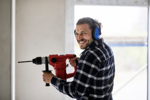 Portrait Of Smiling Worker Using Electric Drill On A Construction Site