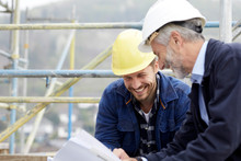 Happy Architect And Worker Discussing Building Plan On Scaffolding On A Construction Site
