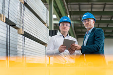 Two Businessmen Wearing Hard Hats And Safety Goggles In A Factory Using Tablet