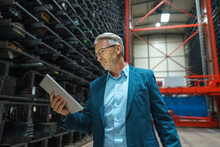 Mature Businessman Using Tablet In A Factory