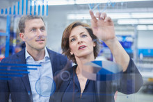 Female Manager Analyzing Graph With Male Supervisor On Glass In Industry