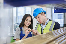Female Worker And Supervisor Examining Metallic Bolt In Factory
