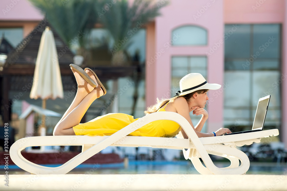 Fototapeta Young woman is lying on beach chair working on computer laptop connected to wireless internet typing text on keys in summer resort. Doing business while travelling concept.
