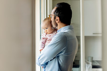 Father With Baby Looking Out O...