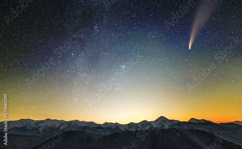 Fototapeta Surreal view of night in mountains with starry dark blue cloudy sky and C/2020 F3 (NEOWISE) comet with light tail