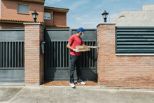Male Postal Worker Using Intercom While Standing With Package At House Gate