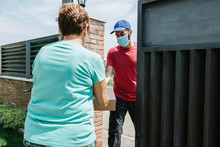 Senior Woman Receiving Delivery Package From Postal Worker At Gate