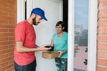 Postal Worker Showing Digital Tablet To Senior Woman For Signature At Doorway