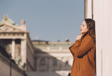 Young Woman In Toffee Brown Coat Leaning Against The Wall
