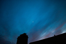 A Bright Blue And Purple Night Sky Over A Silhouetted Roof With A Chimney
