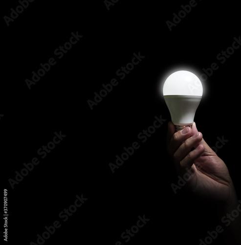 Fototapeta Lit lightbulb held in hand on black background