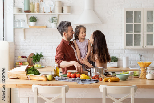 Tablou Canvas Happy parents with daughter cooking on kitchen