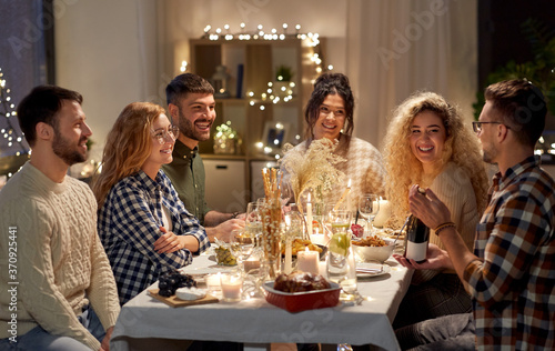 holidays and celebration concept - happy friends having christmas dinner at home with bottle of non-alcoholic red wine