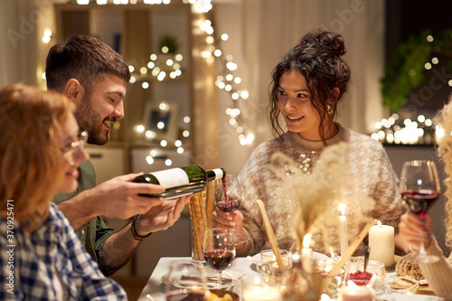 holidays and celebration concept - happy friends having christmas dinner at home pouring non-alcoholic red wine