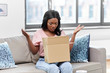 delivery, shipping and people concept - upset young african american woman opening parcel box with clothes at home