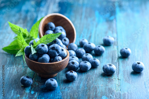 Foto Bowl of fresh blueberries on blue rustic wooden table closeup.