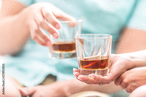 фотография Man and woman hands toasting with glasses of whiskey brandy or rum indoors - clo