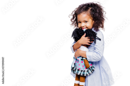 Photo Portrait of a cute little african american girl hugging doll, isolated on white background