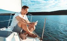 Man Using Smartphone Sitting On Deck Sailing Across Sea Outdoors