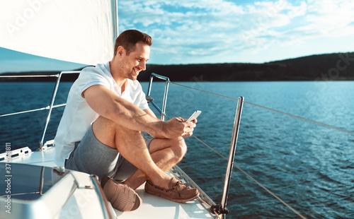 Obraz na płótnie Man Using Smartphone Sitting On Deck Sailing Across Sea Outdoors