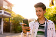 Happy young handsome Indian teenage boy using phone outdoors