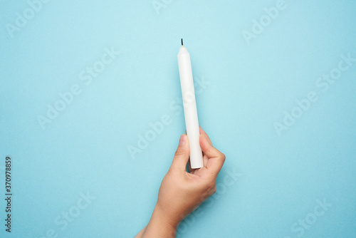 Fotografia female hand holding a white wax candle on a blue background