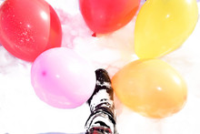 A Booted Foot Stands In The Snow Among Multicolored Balloons
